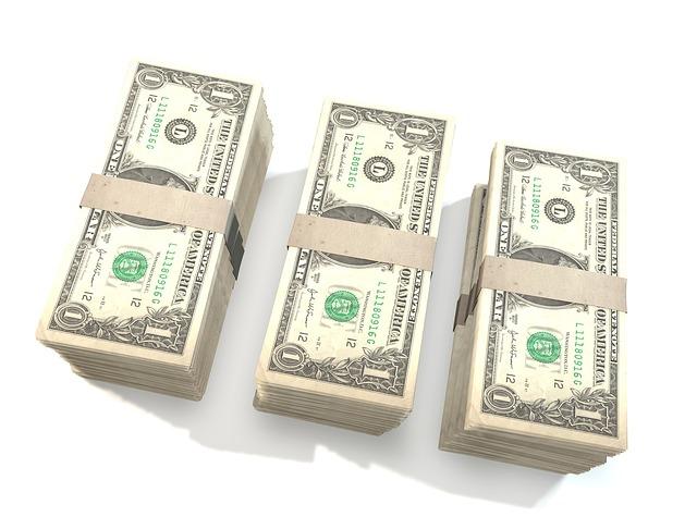 tři hromádky dolarovek