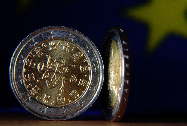 dvě lesklé euromince postavené na hranu