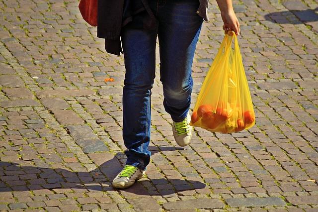 žena nese nákup v igelitové tašce