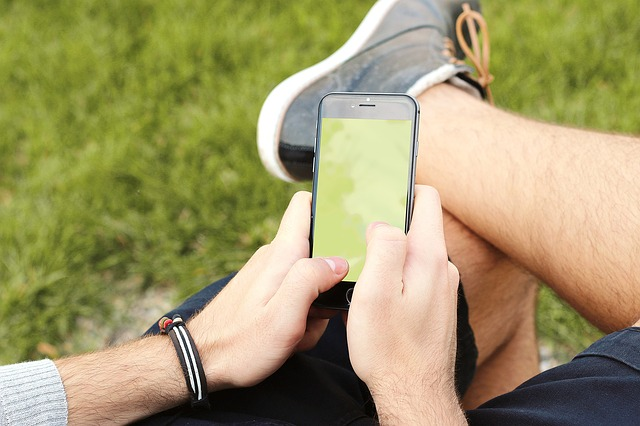 Muž hrající si s telefonem na lavičce